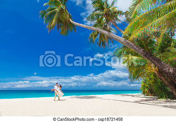 young loving happy couple on tropical beach with palm trees, wedding on beach - csp18721458