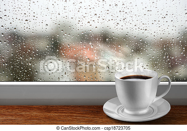 Coffee cup against window with rainy day view