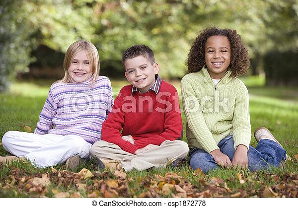 Group of children sitting in garden - csp1872778