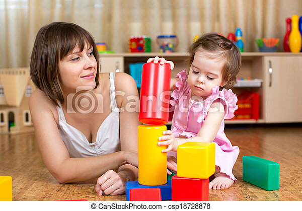 mom and child play block toys indoors - csp18728878