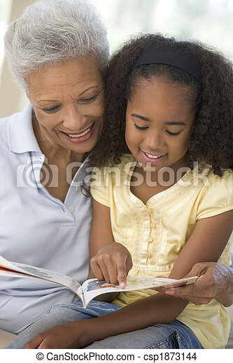 Grandmother and granddaughter reading and smiling - csp1873144