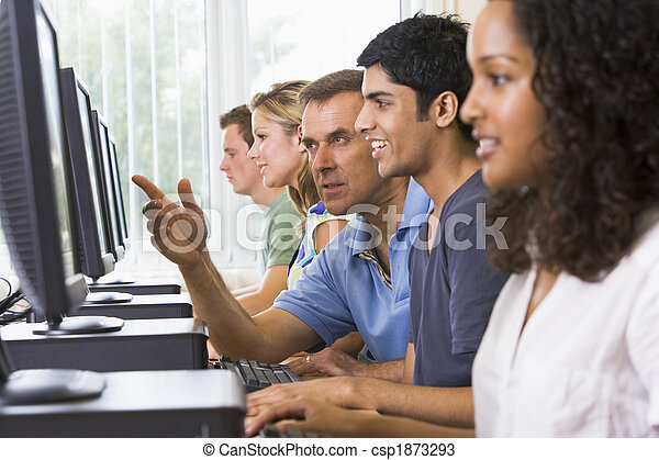 Teacher assisting college student in a computer lab - csp1873293