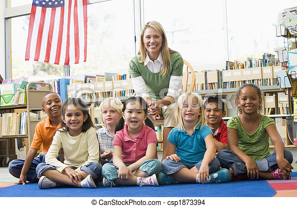 Kindergarten teacher sitting with children in library - csp1873394