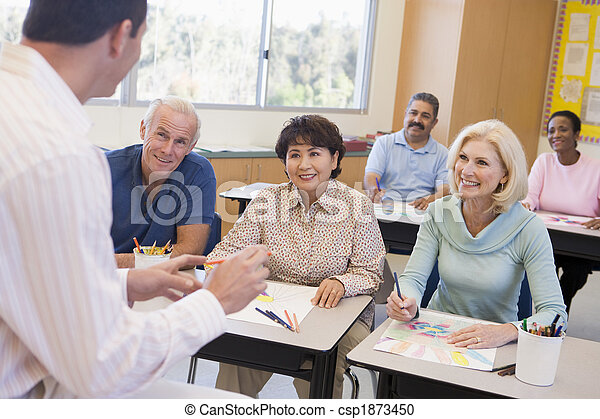 Adult students in class drawing pictures with teacher in foreground (selective focus) - csp1873450