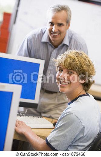 A teacher talks to a schoolboy using a computer in a high school - csp1873466