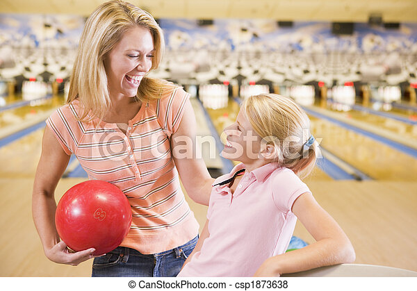 Woman and young girl in bowling alley holding ball and smiling - csp1873638