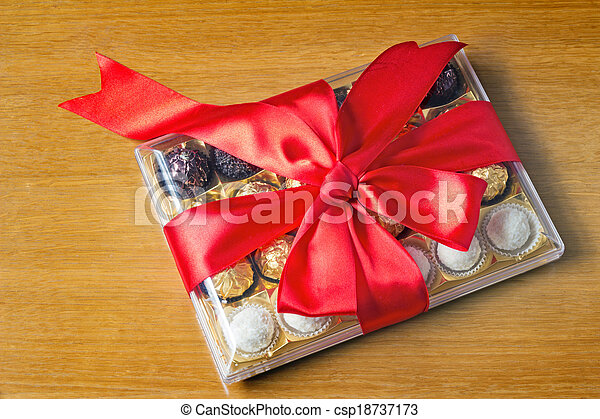 A beautifully decorated and tied with a ribbon box of chocolates, gift by a holiday, celebration, anniversary. - csp18737173