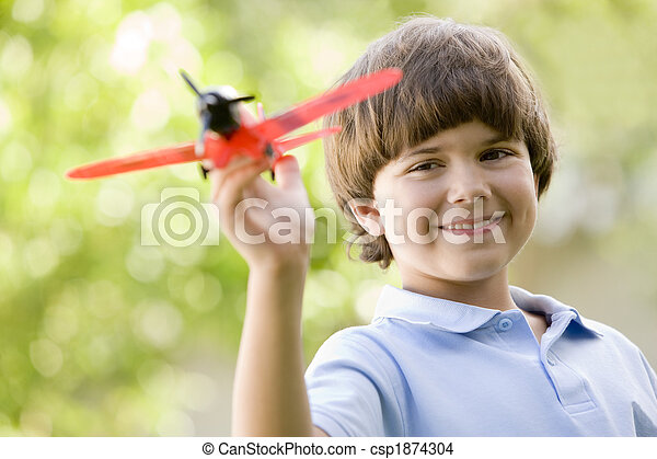 Young boy with toy airplane outdoors smiling - csp1874304