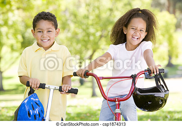 Brother and sister outdoors with scooter and bicycle smiling - csp1874313