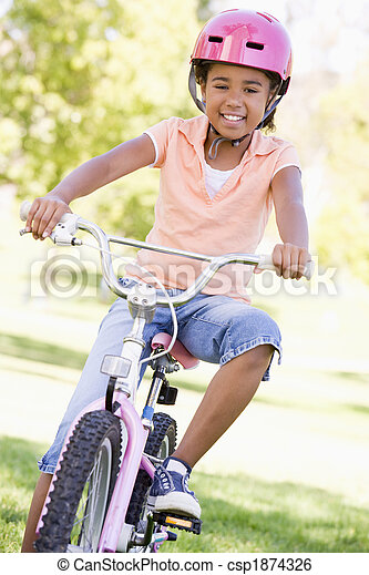 Young girl on bicycle outdoors smiling - csp1874326