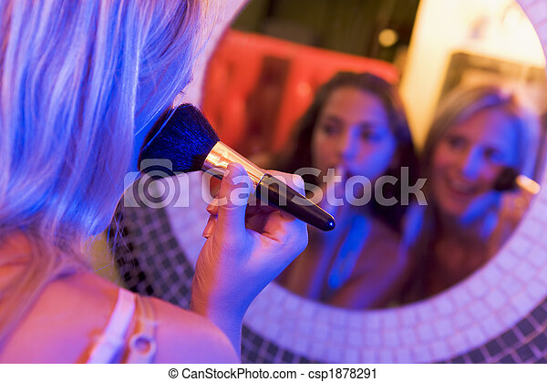 Two young women applying makeup in a nightclub bathroom - csp1878291