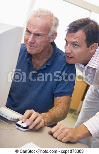 Mature male student learning computer skills - csp1878383