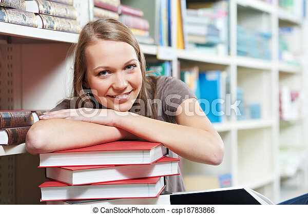 Smiling young adult woman reading  book in library - csp18783866