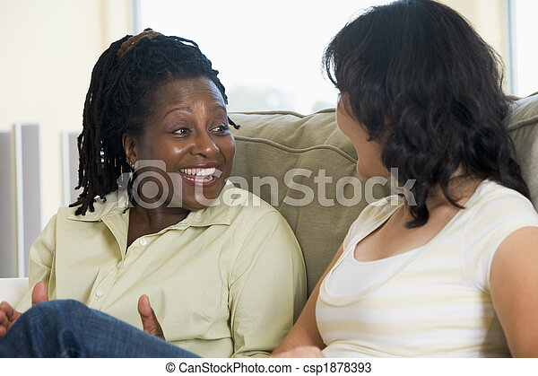 Two women talking in living room and smiling - csp1878393