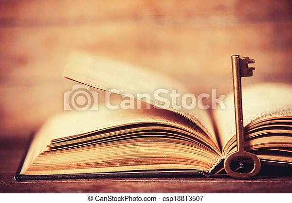 Retro key and opened book - csp18813507