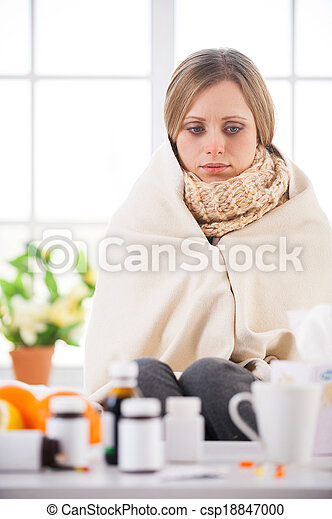 Sick and hopeless. Young woman covered with plaid looking at the medicines while sitting in bed at her apartment
