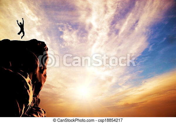A silhouette of a man jumping for joy on the peak of the mountain, cliff at sunset - csp18854217