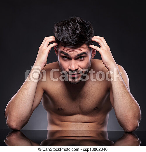 naked young man scratches head