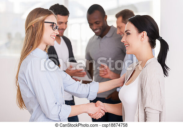 Women shaking hands. Two beautiful young women handshaking while group of people communicating on background - csp18874758