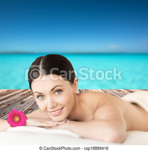 smiling woman lying on the massage desk