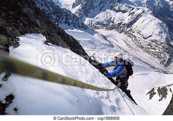 Young men mountain climbing on snowy peak - csp1888958