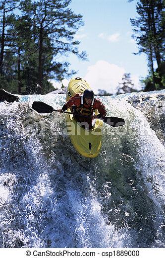 Young man kayaking down waterfall - csp1889000