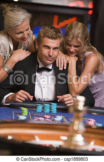 Man gambling in casino surrounded by attractive women - csp1889803