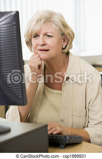 Confused woman frowning at computer monitor - csp1889931