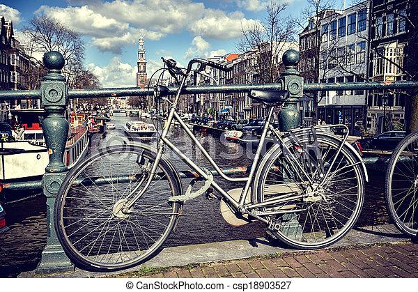 Old bicycle on bridge. Amsterdam cityscape - csp18903527