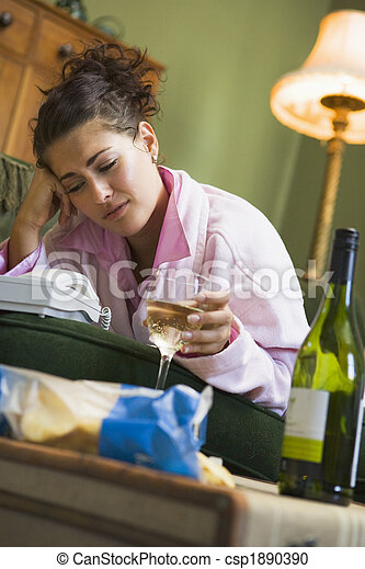 A young woman in her pyjamas drinking wine and watching her tele - csp1890390