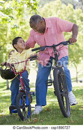 Grandfather and grandson on bikes outdoors smiling - csp1890727