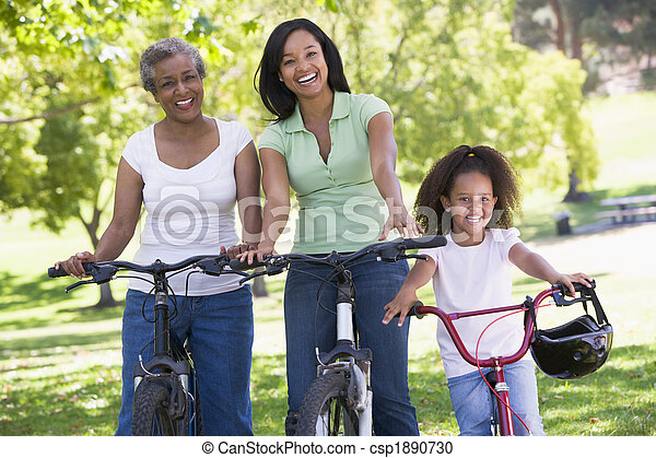 Grandmother with adult daughter and grandchild riding bikes - csp1890730