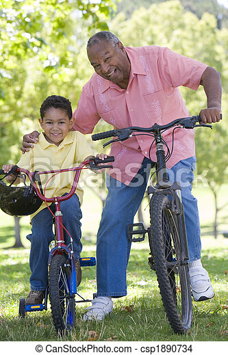 Grandfather and grandson on bikes outdoors smiling - csp1890734