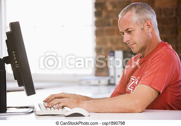 Businessman in office typing on computer - csp1890798