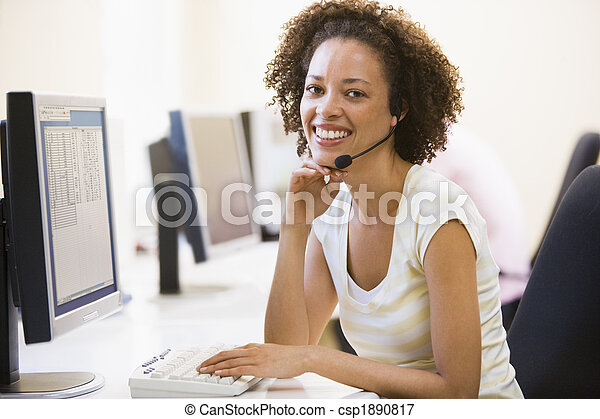 Woman wearing headset in computer room smiling - csp1890817