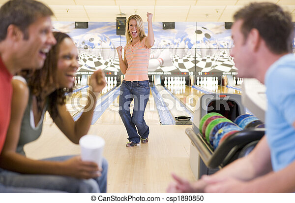 Four young adults cheering in a bowling alley - csp1890850