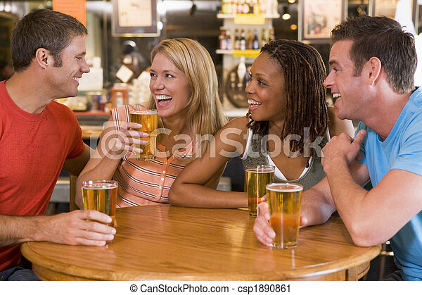 Group of young friends drinking and laughing in a bar - csp1890861