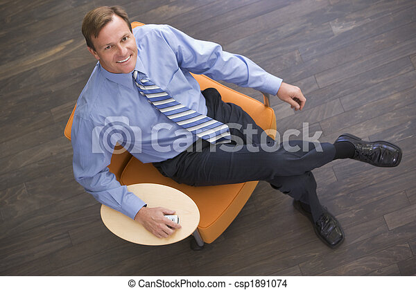 Businessman sitting indoors with cellular phone smiling - csp1891074