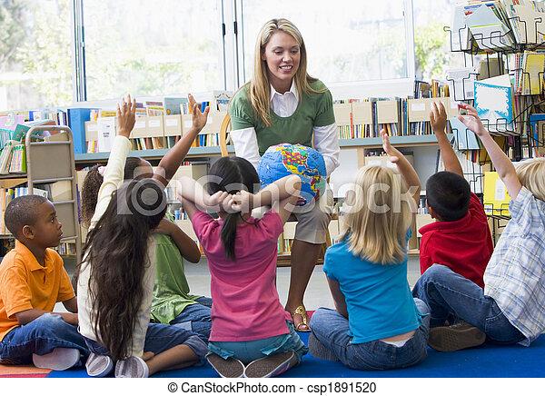 Kindergarten teacher and children with hands raised in library - csp1891520
