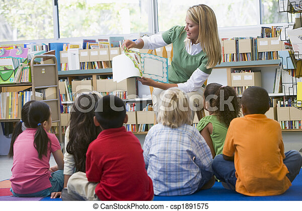 Kindergarten teacher reading to children in library - csp1891575