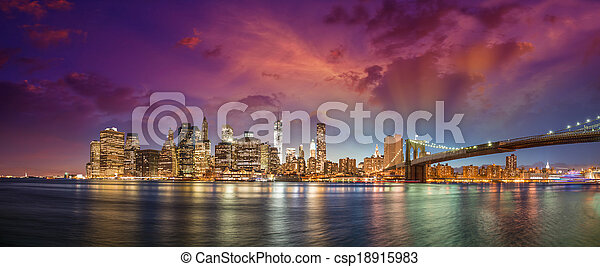 New York City Manhattan skyline panorama with Brooklyn Bridge and office skyscrapers buildings at dusk illuminated with lights at night. - csp18915983