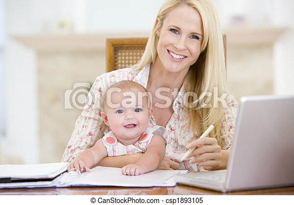 Mother and baby in dining room with laptop smiling - csp1893105