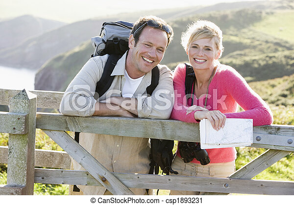 Couple on cliffside outdoors leaning on railing and smiling - csp1893231