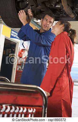 Two mechanics working under car smiling - csp1893372