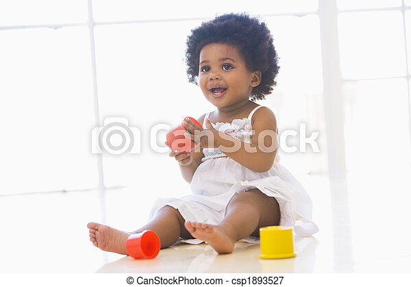 Baby indoors playing with cup toys - csp1893527