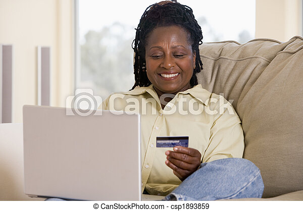 Woman in living room using laptop holding credit card and smilin - csp1893859