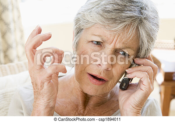 Woman indoors using cellular phone frowning - csp1894011