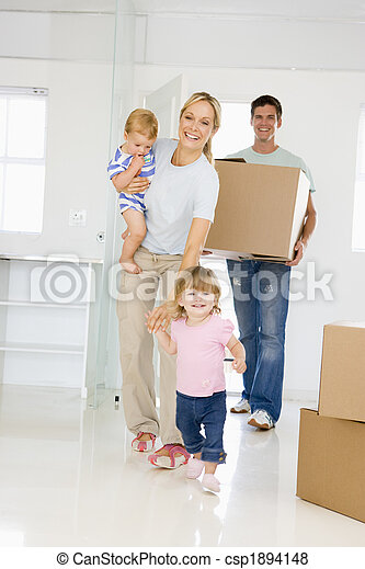 Family with box moving into new home smiling - csp1894148