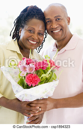 Husband and wife holding flowers smiling - csp1894323