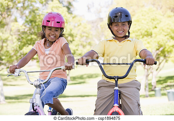 Brother and sister outdoors on bicycles smiling - csp1894875